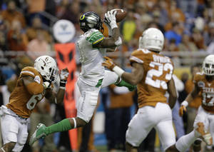 Photo - Oregon's Josh Huff, center, pulls in a pass as Texas' Quandre Diggs (6) defends during the second half of the Valero Alamo Bowl NCAA college football game, Monday,  Dec. 30, 2013, in San Antonio. Oregon won 30-7. (AP Photo/Eric Gay)
