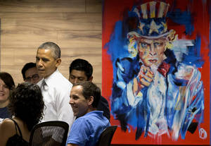 """Photo - President Barack Obama stands next to a painting of """"Uncle Sam,"""" during a visit with workers at 1776, a hub for tech startups, Thursday, July 3, 2014, in Washington. The president said  job growth in June shows the recovery is taking hold, but the economy could still do better, he also urged Congress to work with him to help create more jobs.  (AP Photo/Jacquelyn Martin)"""