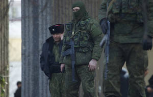 Photo - Unidentified gunmen wearing camouflage uniforms block the entrance of the Crimean Parliament building in Simferopol, Ukraine, Saturday, March 1, 2014. The discord between Russia and Ukraine sharpened Saturday when the pro-Russian leader of Ukraine's Crimea region claimed control of the military and police and appealed to Russia's president for help in keeping peace there. (AP Photo/Ivan Sekretarev)