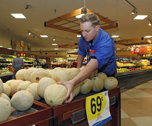 photo -   Produce manager Nate Codina arranges a display of Rocky Ford cantaloupes at a Denver Kings Soopers market on Friday, July 13, 2012. Colorado cantaloupes are back in supermarkets Friday, and growers of the Rocky Ford melons are going on the offensive to restore the fruit's reputation a year after Colorado melons caused a deadly nationwide listeria outbreak. Farmers have banded together to trademark the melons and fund a new tracking system to prevent future outbreaks. (AP Photo/Ed Andrieski)