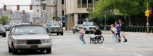 Photo - DOWNTOWN STREETS: A woman in a wheelchair and children hurry to cross N Hudson Avenue between the County Courthouse and City Hall in downtown Oklahoma City in this 2009 photo. <strong>Jim Beckel - The Oklahoman</strong>