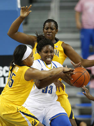 photo - UCLA forward Jasmine Dixon, center, is defended by California guard Brittany Boyd, left, and Talia Caldwell during the first half of an NCAA college basketball game in Los Angeles, Friday, Feb. 15, 2013. (AP Photo/Jae C. Hong)