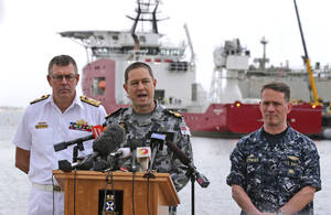 Photo - FILE - In this Sunday, March 30, 2014 file photo, Royal Australian Navy Commodore Peter Leavy, center, commander of joint task force 658, accompanied by U.S. Navy Captain Mark Matthews, right, and Chief of the Royal Australian Navy Vice Admiral Ray Griggs, speak at a press conference at naval base HMAS Stirling about the Australian navy ship Ocean Shield, shown in the background, and her roll in the search for missing Malaysia Airlines Flight MH370 in Perth, Australia. It's not a question most governments involved in the hunt for the jetliner care to answer: How much has the far-flung, month-long search cost? The U.S. bill alone has run into the millions of dollars, and Australia is spending more than half a million dollars a day on just one of the ships it has in the Indian Ocean. (AP Photo/Rob Griffith, File)