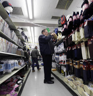 Photo - Marty Grossman shops for a hat at Lodge's store on in Albany, N.Y. Retail sales totaled $421.4 billion in February. Adjusted for inflation, that was nearly 18 percent above the recession low and just 0.7 percent below the record level in November 2007. AP Photo