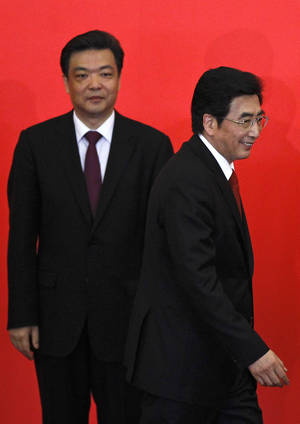 Photo - <p>In this July 3, 2012 photo, Beijing mayor and newly-elected Beijing Municipal Communist Party Secretary Guo Jinlong, right, walks past vice mayor Ji Lin, back, during a press conference to introduce the city's top Communist Party leaders in Beijing, China. The People's Daily newspaper says Beijing's mayor and the vice mayor have resigned in what is likely a routine reshuffling but which comes amid public questioning of the government's handling of rainstorms that left at least 37 dead in the capital. (AP Photo/Alexander F. Yuan)</p>