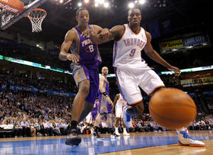 photo - Oklahoma City Thunder power forward Serge Ibaka (9) and Phoenix Suns center Channing Frye (8) go after a loose ball during the NBA basketball game between the Oklahoma City Thunder and the Phoenix Suns at the Chesapeake Energy Arena on Wednesday, March 7, 2012 in Oklahoma City, Okla.  Photo by Chris Landsberger, The Oklahoman