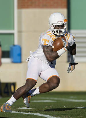 Photo - In this March 7, 2014 photo, University of Tennessee running back Marlin Lane participates in a drill during spring practice in Knoxville, Tenn. One year ago, Lane missed the end of spring practice for disciplinary reasons and had to work his way toward reinstatement. Now he's earning raves for continuing to practice and help lead a young offense despite dealing with a hand injury.(AP Photo/The Knoxville News Sentinel, Paul Efird)
