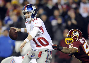 Photo - New York Giants quarterback Eli Manning (10) looks to pass as Washington Redskins inside linebacker Perry Riley hangs onto his jersey during the second half of an NFL football game Sunday, Dec. 1, 2013, in Landover, Md. (AP Photo/Nick Wass)