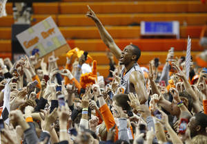 Photo - OSU's Markel Brown celebrates with fans after Saturday night's upset victory against Kansas.                    Photo by Bryan Terry, The Oklahoman