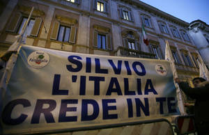 "photo - Supporters of former Italian premier Silvio Berlusconi expose a banner reading ""Silvio Italy trusts you"" in front of Palazzo Grazioli, the residence of Berlusconi, in Rome, Thurdsday, Dec. 6, 2012. The 76-year-old Berlusconi has been hinting at a comeback, after earlier saying he would leave the party to a younger candidate. Berlusconi claims allies are pressing him to return, hoping that Monti's painful austerity measures will win votes for the center-right. Lawmakers belonging to Silvio Berlusconi's center-right party abstained Thursday from a confidence vote in the government of Premier Mario Monti, raising questions over its future and the progress of its economic reform program. (AP Photo/Alberto Pellaschiar)"