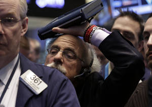 Photo - Trader Peter Tuchman rests his handheld device on his head as he works on the floor of the New York Stock Exchange Friday, Jan. 31, 2014. Stocks fell sharply in early trading Friday, as investors fretted over disappointing earnings from companies like Amazon.com and more trouble in overseas markets. (AP Photo/Richard Drew)