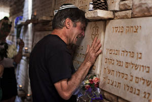 Photo -   An Israeli man cries beside a memorial stone for a fallen soldier during the annual Memorial Day ceremony at the Mt. Herzl military cemetery in Jerusalem, Wednesday, April 25, 2012. (AP Photo/Bernat Armangue)