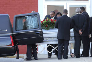 photo - Pallbearers place a coffin with the body of Kansas City Chiefs NFL football player Jovan Belcher into a hearse after a service at the Landmark International Deliverance and Worship Center Wednesday, Dec. 5, 2012 in Kansas City, Mo. Belcher shot his girlfriend, Kasandra Perkins, at their home Saturday morning before driving to Arrowhead Stadium and turning the gun on himself.  (AP Photo/Ed Zurga)