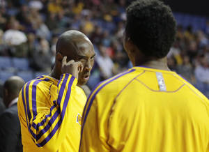 Photo - Los Angeles Lakers' Kobe Bryant, left, talks to Nick Young before an NBA preseason basketball game against the Denver Nuggets on Tuesday, Oct. 8, 2013, in Ontario, Calif. (AP Photo/Jae C. Hong)
