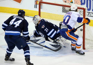Photo - New York Islanders' Michael Grabner (40) scores on Winnipeg Jets goaltender Ondrej Pavelec (31) as Zach Bogosian (40) watches during overtime of an NHL hockey game in Winnipeg, Manitoba, Tuesday, March 4, 2014. The Islanders won 3-2. (AP Photo/The Canadian Press, Trevor Hagan)
