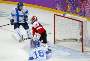 Photo - Finland forward Teemu Selanne (8) watches as the puck slips past Austria goaltender Bernhard Starkbaum for a goal in the first period of a men's ice hockey game at the 2014 Winter Olympics, Thursday, Feb. 13, 2014, in Sochi, Russia. (AP Photo/Mark Humphrey)