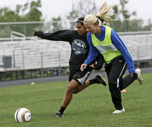 photo - Tayler Shoopman, left, tries to get the ball past Ashley Garver during soccer practice at Piedmont High School in Piedmont, Okla., Wednesday, April 11, 2012. Photo by Nate Billings, The Oklahoman