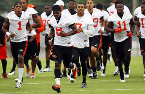Photo - Oklahoma State safety Daytawion Lowe leads the defense while running across the field at practice on August 2, 2013 in preparation for the fall season. Photo by KT KING, The Oklahoman