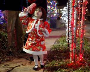 Photo - Maisy Root, 3, looks at Christmas lights Wednesday outside The Children's Hospital at OU Medical Center before a news conference. Maisy was born in China with a facial deformity. Amy and Benjamin Root, of Oklahoma City, adopted her, and she underwent reconstructive surgery. Photo by Bryan Terry, The Oklahoman