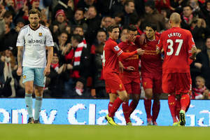 Photo - Liverpool's Luis Suarez, centre right, celebrates the opening goal which was credited as an own goal scored by West Ham's Guy Demel, not in view, during their English Premier League soccer match at Anfield, Liverpool, England, Saturday, Dec. 7, 2013. (AP Photo/ PA, Peter Byrne)