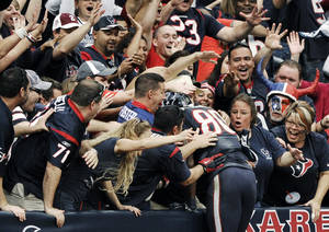 photo -   Houston Texans wide receiver Andre Johnson (80) dives into the crowd after scoring the winning touchdown against the Jacksonville Jaguars in overtime of an NFL football game, Sunday, Nov. 18, 2012, in Houston. The Texans won 43-37. (AP Photo/Dave Einsel)