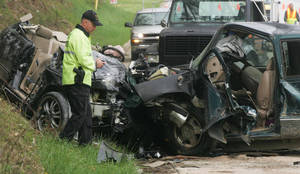 Photo -   FILE - In this April 19, 2009 file photo, North Carolina Highway Patrolman R. Grayson investigates a two-vehicle wreck on U.S. 64 near Brevard, N.C., that killed three people, including a child, in the head-on collision. A freak accident on New York's Bronx River Parkway that wiped out three generations of a family on April 29, 2012, is being touted by some transportation advocates as more evidence that New York City's aging highway system needs major upgrades. Yet, while New York City saw 243 people killed in traffic accidents in 2011, by comparison, North Carolina, a state with a population not much larger than New York City, had 1,314 motor vehicle fatalities in 2009. (AP Photo/Times-News, Mike Dirks, File)