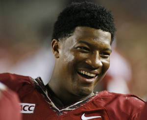Photo - Florida State quarterback Jameis Winston (5) smiles on the sidelines in the fourth quarter of an NCAA college football game against Syracuse on Saturday, Nov. 16, 2013, in Tallahassee, Fla. Florida State best Syracuse 59-3. (AP Photo/Phil Sears)