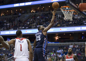 Photo - Charlotte Bobcats center Al Jefferson (25) scores during the first half of an NBA basketball game against the Washington Wizards on Wednesday, March 12, 2014, in Washington. Wizards forwards Trevor Ariza (1) and Trevor Booker watch. The Bobcats won 98-85. (AP Photo/ Evan Vucci)