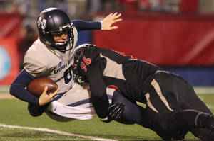Photo - Fresno State's Todd Hunt sacks Utah State's Darell Garretson in the first half of an NCAA college football game in Fresno, Calif., Saturday, Dec. 7, 2013. (AP Photo/Gary Kazanjian)