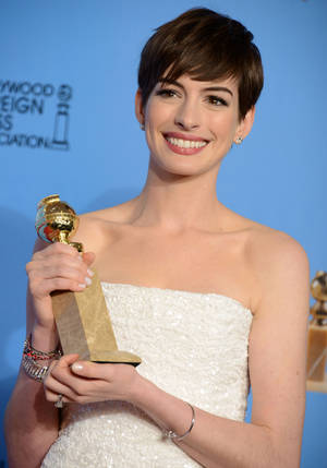 "Photo - FILE - In this Jan. 13, 2013 file photo, Anne Hathaway poses with the award for best performance by an actress in a supporting role in a motion picture in ""Les Miserables"" backstage at the 70th Annual Golden Globe Awards at the Beverly Hilton Hotel, in Beverly Hills, Calif. Actors and actresses compete separately at awards shows, a tradition some in the industry consider vital for women but others question. (Photo by Jordan Strauss/Invision/AP, File)"