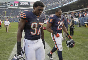 Photo - Chicago Bears linebacker J.T. Thomas (97) and running back Michael Bush (29) leave the field after the Bears' 23-17 loss in overtime to the Seattle Seahawks overtime in an NFL football game in Chicago, Sunday, Dec. 2, 2012.  (AP Photo/Nam Y. Huh)
