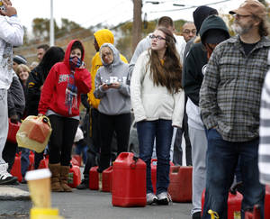 Photo -   As temperatures begin to drop, people wait in line to fill containers with gas at a Shell gasoline filling station Thursday, Nov. 1, 2012, in Keyport, N.J. In parts of New York and New Jersey, drivers lined up Thursday for hours at gas stations that were struggling to stay supplied. The power outages and flooding caused by Superstorm Sandy have forced many gas stations to close and disrupted the flow of fuel from refineries to those stations that are open. (AP Photo/Mel Evans)