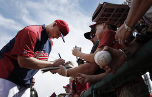 Photo - Cleveland Indians pitcher Justin Masterson signs autographs before an exhibition baseball game against the Cincinnati Reds in Goodyear, Ariz., Wednesday, Feb. 26, 2014. (AP Photo/Paul Sancya)