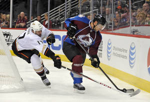 Photo - Anaheim Ducks left wing Dustin Penner (17) and Colorado Avalanche defenseman Jan Hejda (8), from the Czech Republic, chase the puck into the corner during the second period of a preseason NHL hockey game, Wednesday, Sept. 18, 2013, in Denver. (AP Photo/Jack Dempsey)