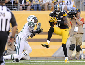 Photo -   Pittsburgh Steelers wide receiver Mike Wallace (17) makes a catch for a touchdown in front of New York Jets cornerback Antonio Cromartie (31) in the third quarter of an NFL football game on Sunday, Sept. 16, 2012, in Pittsburgh. The touchdown call was confirmed after replay. (AP Photo/Don Wright)