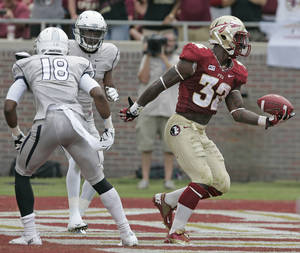Photo - Florida State's James Wilder Jr., right, scores in the third quarter against Nevada's defense in an NCAA college football game on Saturday, Sept. 14, 2013, in Tallahassee, Fla. Florida State won the game 62-7. (AP Photo/Steve Cannon)