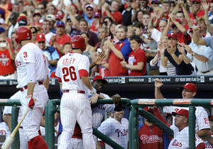 Photo -   Philadelphia Phillies' Chase Utley is greeted by his team and fans after his home run against the Pittsburgh Pirates in the first Inning inning of a baseball game Wednesday, June 27, 2012, in Philadelphia. (AP Photo/Michael Perez)