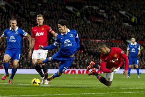 Photo - Manchester United's Patrice Evra, bottom right, attempts to head past Everton's Steven Pienaar, centre, during their English Premier League soccer match at Old Trafford Stadium, Manchester, England, Wednesday Dec. 4, 2013. (AP Photo/Jon Super)