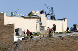 Crews from Standard Roofers are replacing the Spanish tile roof at Sooner Theatre, 101 E Main St., in Norman The roof is being insulated, repaired and retiled. Work should be complete in about a week.  PHOTO BY STEVE SISNEY, THE OKLAHOMAN