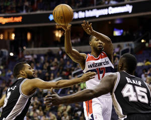 Photo -   San Antonio Spurs guard Patty Mills (8), from Australia, and center DeJuan Blair (45) guard Washington Wizards guard A.J. Price (12) as he passes the ball in the first half of an NBA basketball game Monday, Nov. 26, 2012, in Washington.(AP Photo/Alex Brandon)