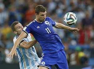Photo - Bosnia's Edin Dzeko shields the ball from Argentina's Hugo Campagnaro during the group F World Cup soccer match between Argentina and Bosnia at the Maracana Stadium in Rio de Janeiro, Brazil, Sunday, June 15, 2014.  (AP Photo/Victor R. Caivano)