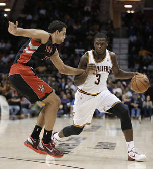 Photo - Cleveland Cavaliers' Dion Waiters (3) drives past Toronto Raptors' Landry Fields (2) during the second quarter of an NBA basketball game Wednesday, Feb. 27, 2013, in Cleveland. Waiters scored a team-high 23 points in the Cavaliers' 103-92 win. (AP Photo/Tony Dejak)