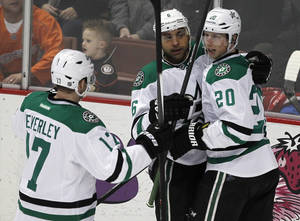Photo - Dallas Stars' Rich Peverley (17) and Cody Eakin (20) congratulate Trevor Daley, left, who scored against the Anaheim Ducks in the second period of an NHL hockey game Saturday, Feb. 1, 2014, in Anaheim, Calif. (AP Photo/Alex Gallardo)