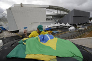 Photo - A Brazilian fan tries to tie his country's flag on top of his car, outside Arena de Sao Paulo, Brazil, on Tuesday, June 10, 2014. The World Cup is set to open on June 12 with Brazil facing Croatia in Sao Paulo. (AP Photo/Thanassis Stavrakis)