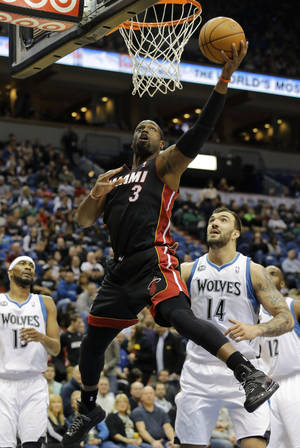 Photo - Miami Heat guard Dwyane Wade (3) goes up to shoot over Minnesota Timberwolves center Nikola Pekovic (14), of Montenegro, and forward Corey Brewer (13) during the first quarter of an NBA basketball game in Minneapolis, Saturday, Dec. 7, 2013. (AP Photo/Ann Heisenfelt)