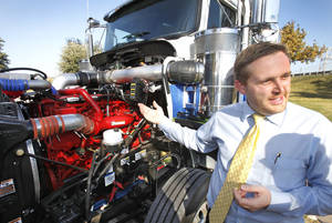 photo - Peake Fuel Solutions has developed a dual-fuel system that allows heavy duty trucks to run on a mixture of diesel and compressed natural gas. Manager of Technology Services Bryan Curtis talks about the natural gas injector on the top of the motor, Friday, November 9, 2012.  Photo By David McDaniel/The Oklahoman