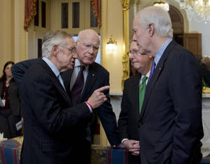 Photo - In this Feb. 12, 2014, photo, Senate Majority Leader Harry Reid, D-Nev., from left, Sen. Patrick Leahy, D-Vt., Republican Leader Mitch McConnell, R-Ky., and Sen. John Cornyn, R-Texas, talk as they wait in the majority leader's office, for a meting King Abdullah II of Jordan, on Capitol Hill in Washington. The meeting came after lawmakers voted on must-pass legislation to increase the government's debt limit and after their leaders decided to drop the parliamentary equivalent of a curtain on the voting until its outcome was assured  (AP Photo/Manuel Balce Ceneta)