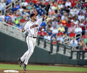 Photo - Virginia second baseman Branden Cogswell (7) leaps for a ball from catcher Nate Irving in the third inning of an NCAA baseball College World Series game in Omaha, Neb., Sunday, June 15, 2014. Mississippi's Errol Robinson was tagged out in a run down on the play.  (AP Photo/Eric Francis)