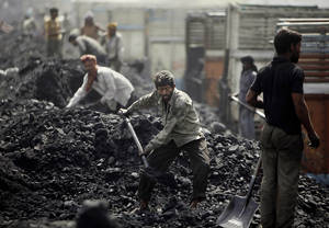 Photo -   FILE- In this Friday, March 23, 2012, file photo, Indian laborers load coal onto trucks at a coal depot on the outskirts of Jammu, India. India's national auditor said Friday, Aug. 17, 2012, the government lost huge sums of money by selling coal fields to private companies without competitive bidding, adding to massive losses from dubious auctions of other state assets. The Comptroller and Auditor General's report to Parliament estimated that private companies got a windfall profit of $34 billion because of the low prices they paid for the fields. (AP Photo/Channi Anand, File)