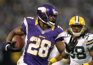 Photo - Minnesota Vikings running back Adrian Peterson, left, runs from Green Bay Packers cornerback Tramon Williams during the first half of an NFL football game Sunday, Dec. 30, 2012, in Minneapolis. (AP Photo/Genevieve Ross)